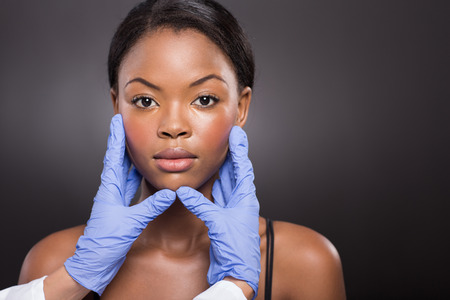plastic surgeon: plastic surgeon checking young african woman face after operation Stock Photo