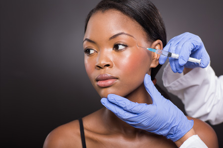 cosmetic surgery: beautiful afro american woman receiving plastic surgery injection on her face Stock Photo