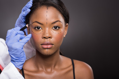 Plastik: junge afrikanische Frau mit Korrekturzeichen f�r Plastische Chirurgie Lizenzfreie Bilder
