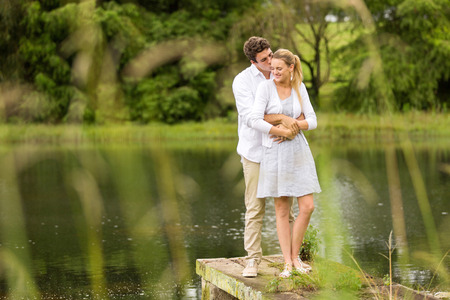 kissing love: romantic young couple standing by the river