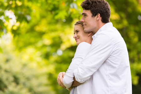 thoughtful young couple hugging outdoors Stock Photo