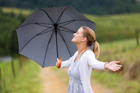 arms open: happy woman with arms open holding umbrella outdoors