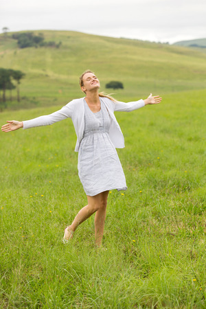 arms open: beautiful carefree young woman arms open in grassland Stock Photo