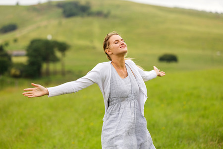 arms open: smiling young woman with arms open on grassland Stock Photo