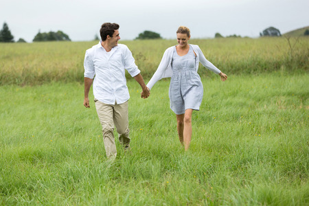 lovely couple: cheerful young couple running in countryside