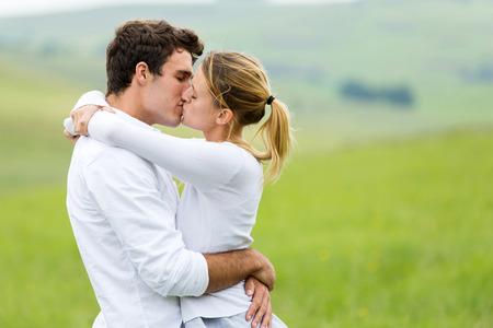 romantic couple kissing outdoors on grassland