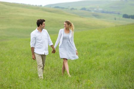 parejas caminando: encantadora pareja de pie en el campo