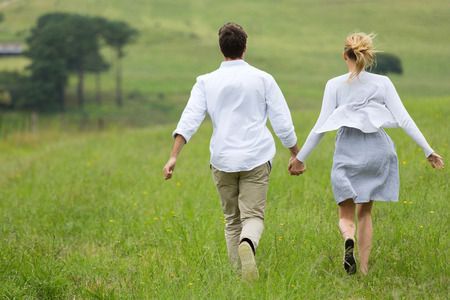lovely couple: lovely couple running together on a green field
