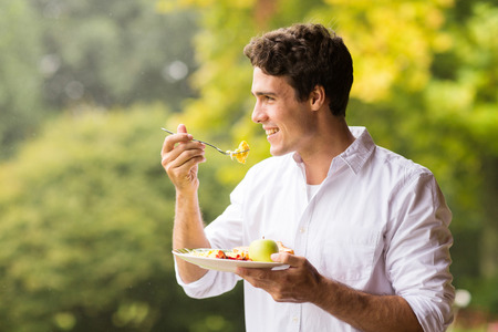 plato del buen comer: apuesto joven de comer huevos revueltos para el desayuno