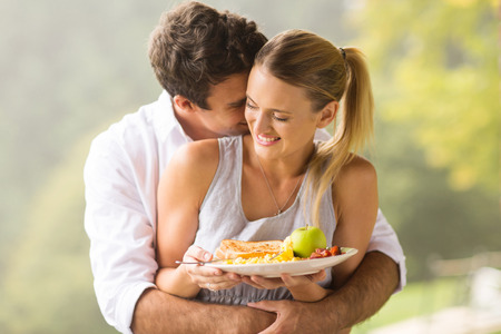 bacon portrait: playful young man hugging girlfriend during breakfast time in the morning Stock Photo