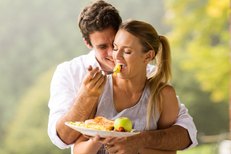 bacon portrait: romantic man feeding wife scrambled eggs for breakfast Stock Photo