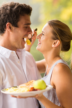 scrambled eggs: cheerful young woman feeding boyfriend breakfast Stock Photo