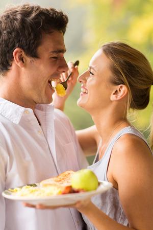 bacon love: cheerful young woman feeding boyfriend breakfast Stock Photo