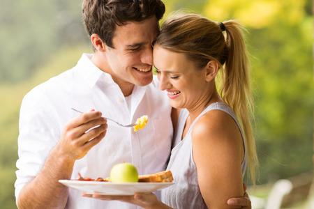 loving husband feeding wife breakfast outdoors