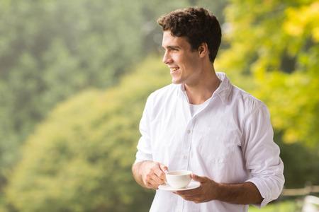 hombre tomando cafe: reflexivo joven que come la taza de caf� al aire libre Foto de archivo