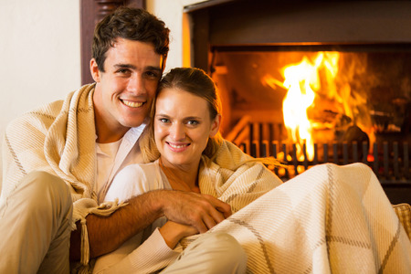 couple on couch: happy couple relaxing on the couch next to fireplace Stock Photo