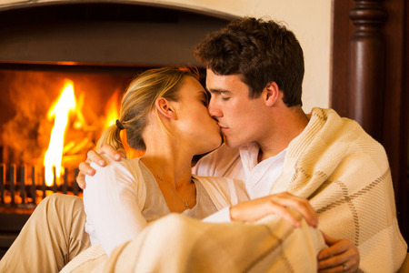 winter wedding: intimate young couple kissing at home in front of fireplace