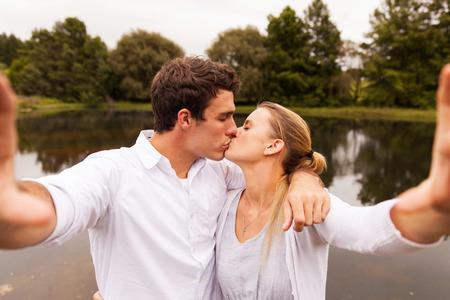 novios besandose: encantadora pareja joven que toma besos Autofoto por el lago