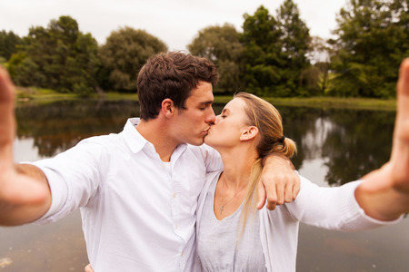 young couple hugging kissing: lovely young couple taking selfie kissing by the lake