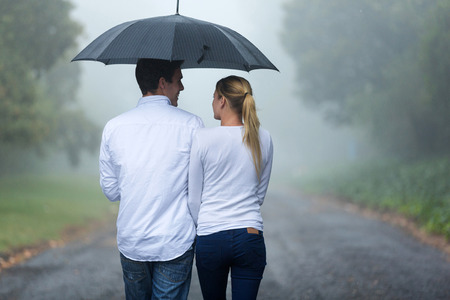 lluvia paraguas: vista posterior del romántica pareja caminando de la lluvia Foto de archivo