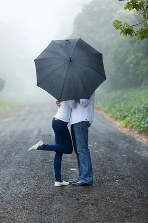 woman with umbrella: romantic young couple hiding behind the umbrella in the rain Stock Photo