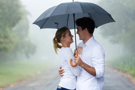 encantadora mujer joven con su novio bajo un paraguas bajo la lluvia
