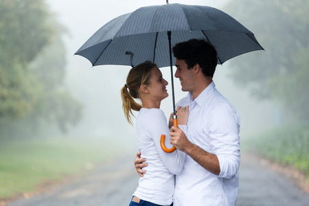 love in rain: lovely young woman with boyfriend under an umbrella in the rain Stock Photo