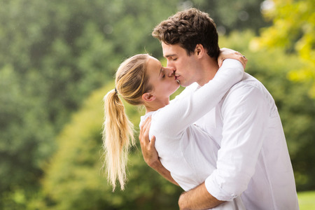 young couple hugging kissing: portrait of romantic couple kissing outdoors