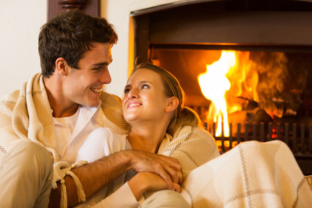 blankets: lovely couple spend a romantic evening by the fireplace