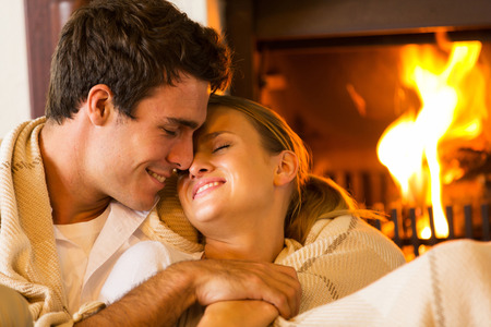 romantic room: loving young couple embracing at home next to fireplace
