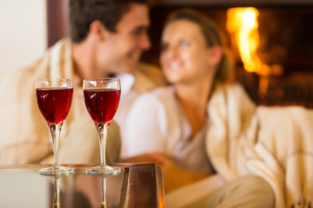 red couch: wine glasses on the table with couple on background Stock Photo