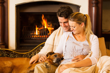 blankets: beautiful young couple sitting by fireplace with their pet dog at home Stock Photo