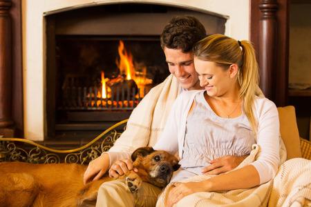 relaxando: bela jovem casal sentado pela chaminé com seu cão de estimação em casa