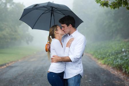 personas besandose: rom�ntica pareja bes�ndose bajo un paraguas Foto de archivo