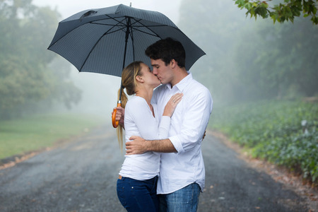 young couple hugging kissing: romantic couple kissing under an umbrella Stock Photo