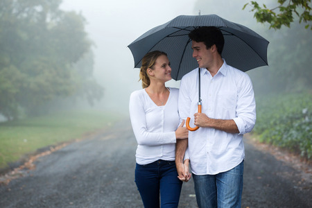 romantic couple: beautiful couple walking under umbrella in forest