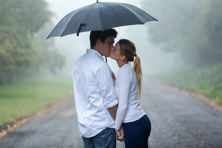 woman with umbrella: loving young couple in love under umbrella in the rain