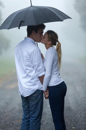 sotto la pioggia: ragazzo e ragazza che baciano sotto l'ombrello sotto la pioggia