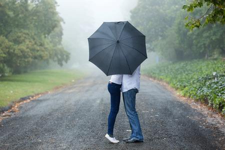 uomo sotto la pioggia: coppia che si bacia dietro l'ombrello nella nebbia