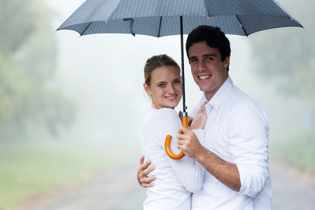 love in rain: happy young couple holding an umbrella in the rain