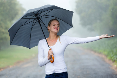 portrait of girl: attractive woman with umbrella enjoying the rain