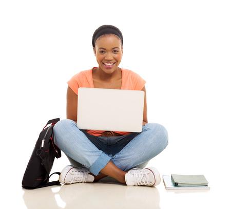 jovenes estudiantes: hembra atractiva estudiante Africana usando la computadora portátil aislados en fondo blanco
