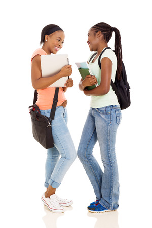 conversation: cheerful young female african college students having conversation on white background Stock Photo