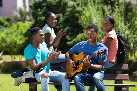 cheerful african college boy playing guitar for friends