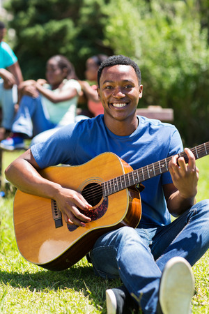 portrait of african college student playing guitar photo