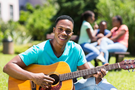 boy playing guitar: handsome male african college boy playing guitar