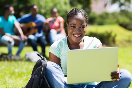 laptop outside: pretty female afro american college student with laptop computer outdoors Stock Photo