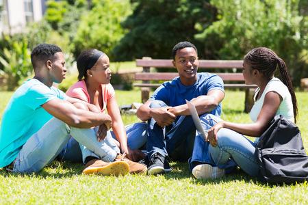 estudiantes adultos: grupo de alegres estudiantes universitarios africanos relajan al aire libre en el campus