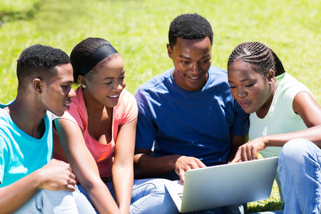 handsome student: group of african university students using laptop outdoors