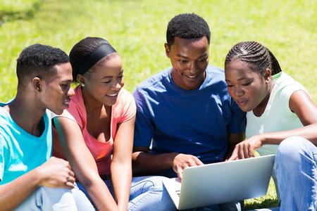 estudiantes adultos: grupo de estudiantes universitarios africanos usan la computadora portátil al aire libre